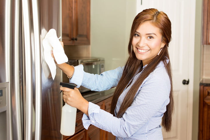 how to clean stainless steel appliances 45484062  woman cleaning her kitchen with a spray bottle