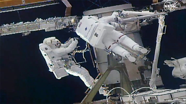(From left) Astronauts Soichi Noguchi and Kate Rubins work to install a solar array modification kit during the fourth spacewalk of 2021.