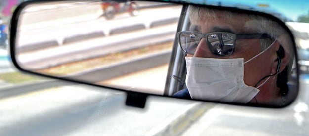 A driver wearing a face mask.