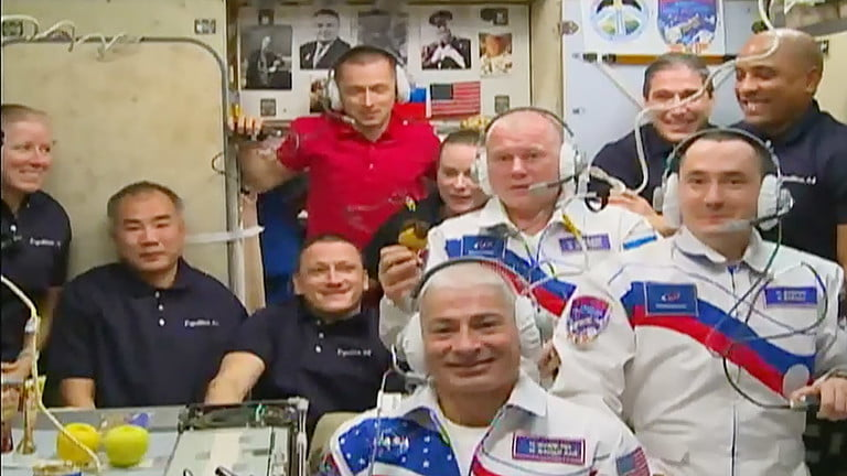 The newly-expanded 10-member station crew gathers in the Zvezda service module for a welcoming ceremony with family members and mission officials on Earth.