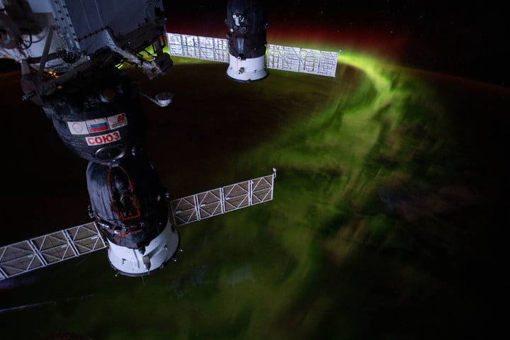 """From the International Space Station's orbit 269 miles above the Indian Ocean southwest of Australia, this nighttime photograph captures the aurora australis, or """"southern lights."""" Russia's Soyuz MS-12 crew ship is in the foreground and Progress 72 resupply ship in the background."""