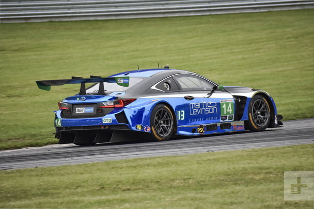 Lexus RC F GT3 driving off on a race track showing off the backside of the car and spoiler