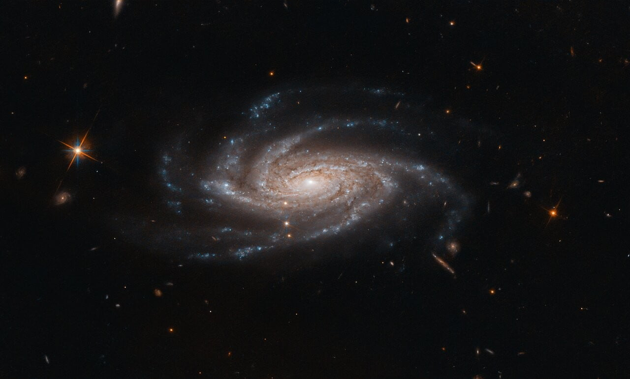 The spiral galaxy NGC 2008 sits centre stage, its ghostly spiral arms spreading out towards us, in this image captured by the NASA/ESA Hubble Space Telescope.