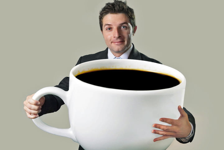 coffee not carcinogenic superheated beverages are young happy business man holding a funny huge and oversized cup of black 15