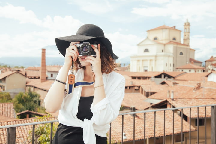 expedia acquisition acquires trover travel photography young woman wearing straw hat photographing old town