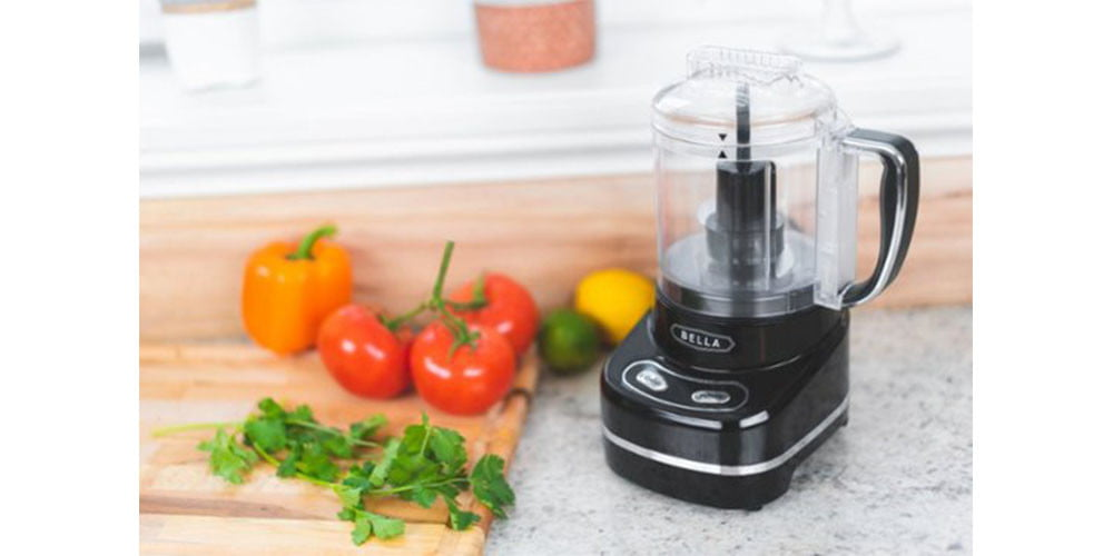 Bella 3-Cup Mini Chopper on a kitchen countertop surrounded by vegetables.