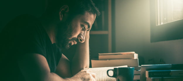 Young man reading a novel with a cup of coffee next to stack of books.