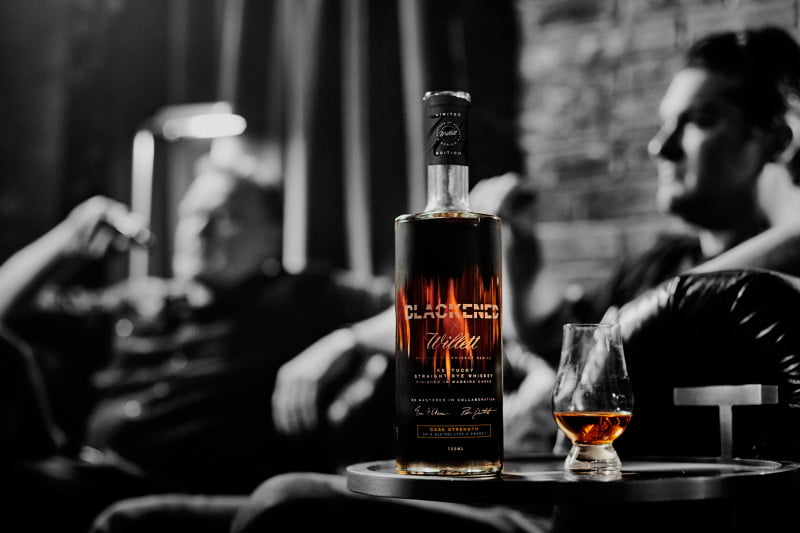Blackened's Rob Dietrich (left) and Willett Distillery's Drew Kulsveen relax behind a bottle of the pair's new rye whiskey.