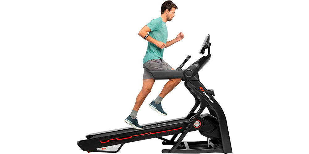 A man running on a Bowflex Treadmill 10 with a white background behind him.