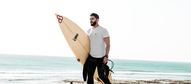 man with surf board walking on the beach.