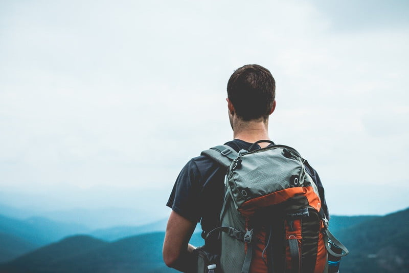 man with backpack facing mountains