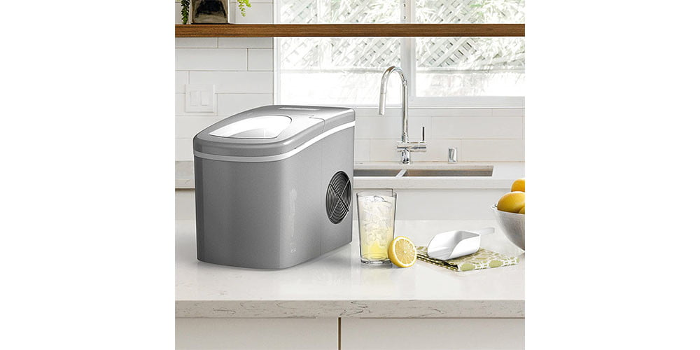 A kitchen environment depicting the Homelabs Chill Pill Countertop Ice Maker next to a sink.