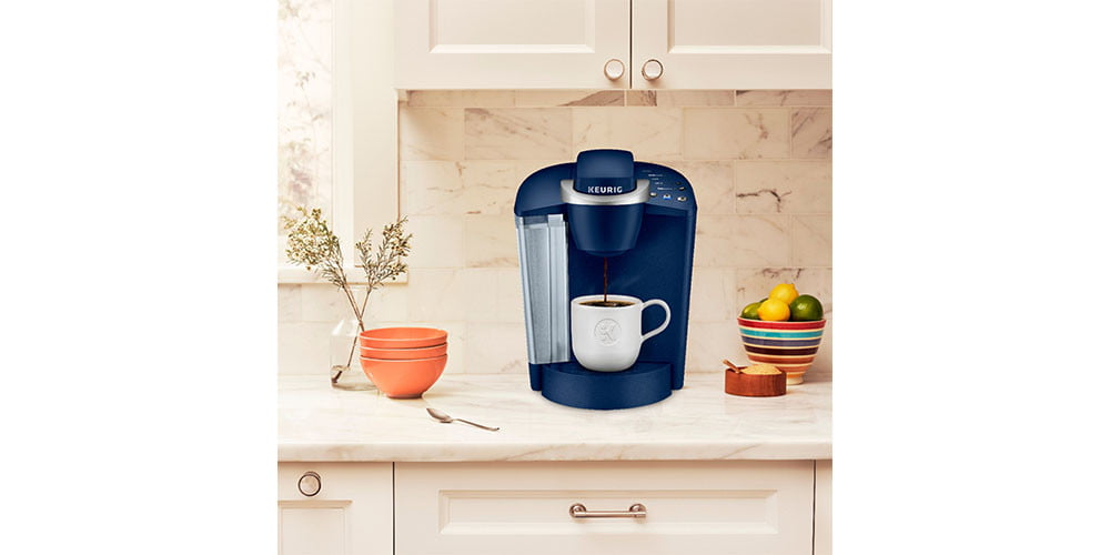 Keurig K-Classic Single Serve K-Cup Pod Coffee Maker placed on a kitchen countertop with plants nearby.