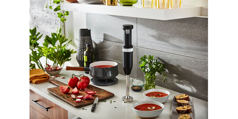 KitchenAid Cordless Variable Speed Hand Blender placed on a kitchen countertop surrounded by food.