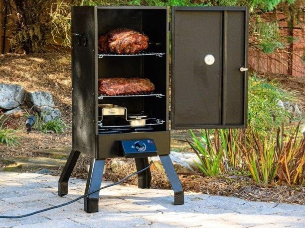 Masterbuilt Analog Electric Smoker with food inside and on the patio.