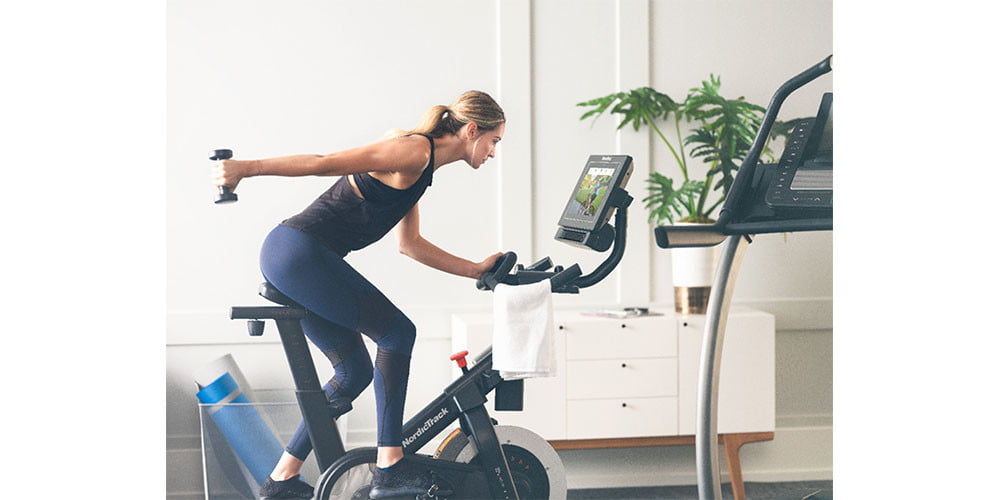A woman riding a NordicTrack Commercial S15i Studio Cycle while holding a dumbbell.