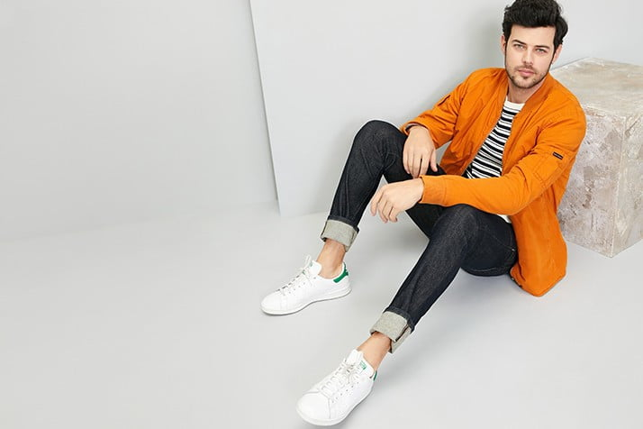 A man seated against a stone block, modeling dark-wash jeans rolled at the cuffs, white sneakers, and an orange jacket over black and white striped shirt.