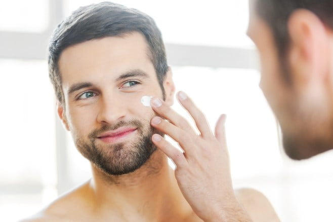 Handsome young shirtless man applying cream at his face and looking at himself with smile while standing in front of the mirror.