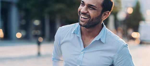 A smiling man wearing a blue shirt in the city.