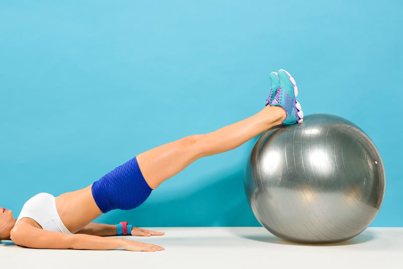 Woman doing hamstring curls with a stability ball.
