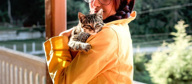 Woman holding a tiger cat against her shoulder